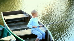 portrait of smiling happy kid fishing in summer from boat - stock footage