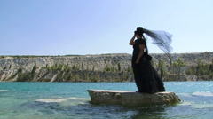 Woman In Black Standing On Cliff  on the Pond Stock Footage