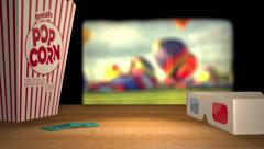 Footage of hot air balloons plays behind 3D glasses, popcorn and tickets Stock Footage