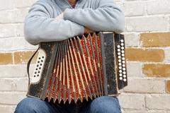 concertina on the man's knee - stock photo