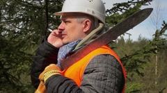 Worker with cell phone and machete in forest Stock Footage