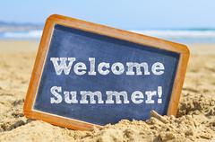 text welcome summer in a chalkboard, on the sand of a beach - stock photo