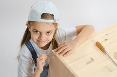 Little girl in dress collector furniture screw screwed Allen - stock photo