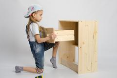 Girl in overalls furniture assembler inserts a drawer chest of drawers Stock Photos