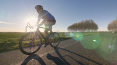 Cyclist man rides bycicle tracking shot slow motion Stock Footage