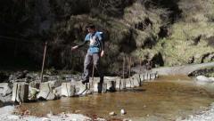 Trekking- Adventure crossing on river rocks Stock Footage