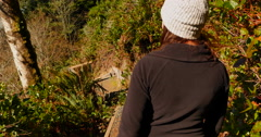 4K Woman Walks Down Earth Cut Steps from Forest out onto West Coast Beach Stock Footage