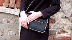 Women with black clutch outdoors against obsolete red brick wall Stock Footage