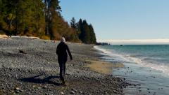 4K Wide Angle Shot of Woman Walking Along Beach, Pacific North Coast Stock Footage