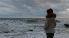 Little girl in inclement weather is on the pier and watching the storm Stock Footage