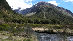 New Zealand Fiordland bubbling river cirque and dark pyramid Stock Footage