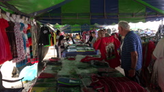 Tourists shop at clothing stall for souvenirs, Phuket, Thailand Stock Footage