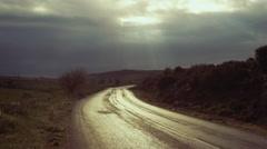 Country road sky opens up shines light rays illuminates path Stock Footage