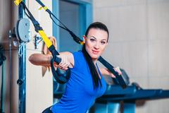 Young attractive woman training with htrx fitness straps in the gym's studio Stock Photos