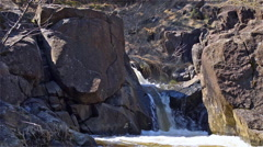 Mountain stream penetrates between the rocks Stock Footage