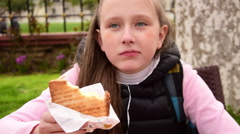 Blonde beautiful teenage girl eating toast heartily at park Stock Footage