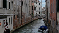Boats tied up for the evening-couple crossing bridge in Venice, Italy Stock Footage