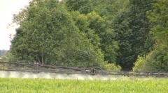 Tractor sprayer sitting stream with fertilizer on crop field Stock Footage