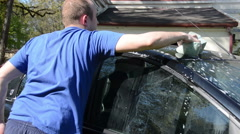 Man with sponge wash automobile car roof in garden yard Stock Footage