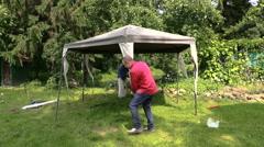 People fix garden tent bower long metal legs Stock Footage