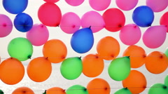 Colorful balloons for target practice floating on a string near sea - stock footage