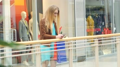 Stock Video Footage of Blonde costs around storefronts and writes message to someone on a mobile phone