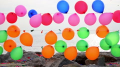 Colorful balloons for target practice floating on a string near sea Stock Footage