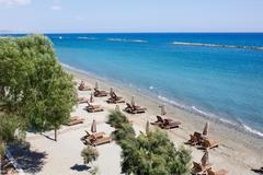 Aerial view on a beach chairs and umbrellas on sand beach. Limassol, Cyprus. - stock photo
