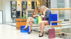 Two young women sitting with shopping bags and smiling Stock Footage
