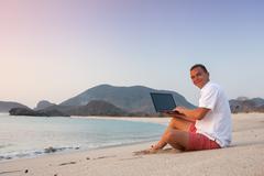 man uses laptop remotely - stock photo