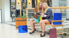 Two young women sitting with shopping bags and smiling. Watching something on a Stock Footage
