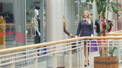 Girls go along and shop talk at the same time, shopping Stock Footage