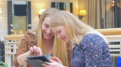 Two blondes sitting on a bench talking, bragging about their purchases Digital - stock footage
