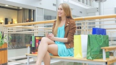 Beautiful young smiling woman holding shopping bags and mobile phone Stock Footage