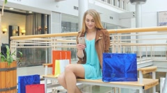 Beautiful blonde sitting on a bench Mall Stock Footage
