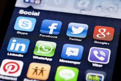 Close-up image of an iPhone screen with icons of social media apps - stock photo