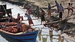Burmese people unloading boat Stock Footage