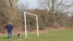 Man Walks his Dog on Rural Field Past Football Goal Posts in Early Morning Light Stock Footage