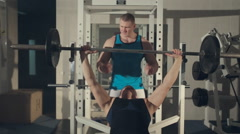 Man training with personal trainer at the gym, pumping iron Stock Footage