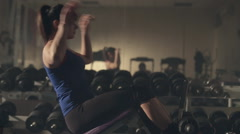 Beautiful young woman doing abdominal exercises on exercise machine in the gym Stock Footage