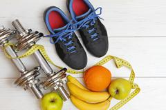 Fitness equipment and healthy nutrition on white wooden plank floor Stock Photos