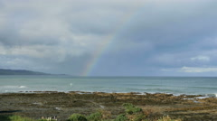 New Zealand Catlins Kaka Point rainbow behind rugged tidepool shelf Stock Footage