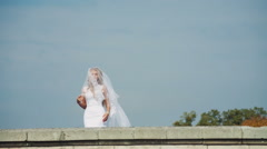 Beautiful bride with a veil that falls from the head when a gust of wind Stock Footage