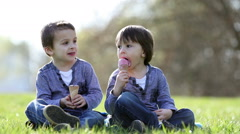 Cute adorable boys, eating ice cream on a sunny spring afternoon in the park Stock Footage