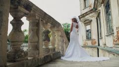 Young beautiful luxurious woman in wedding dress стоячи on stair steps - stock footage