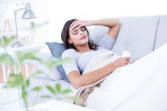 Sick brunette lying on the couch Stock Photos