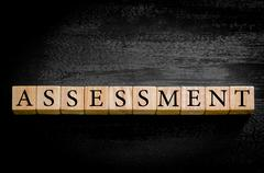Word ASSESSMENT. Wooden small cubes with letters isolated on black background - stock photo