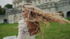 Dynamic video of a beautiful blonde in white dress with long hair. Summer - stock footage