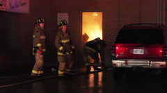Firefighters standing outside a door full of flames Stock Footage