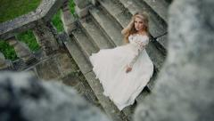 DOLLY MOTION: Beautiful modern bride sitting alone on the stairs of stone Stock Footage